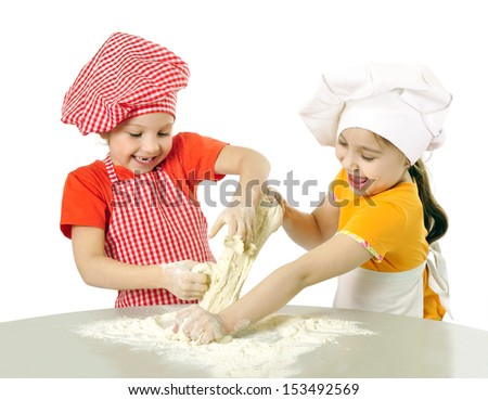 Kids with chef hats preparing the cake dough - stock photo