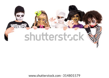 Kids with face-paint and Halloween costumes over a white board - stock photo