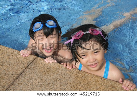 Kids with goggles playing happily in the pool
