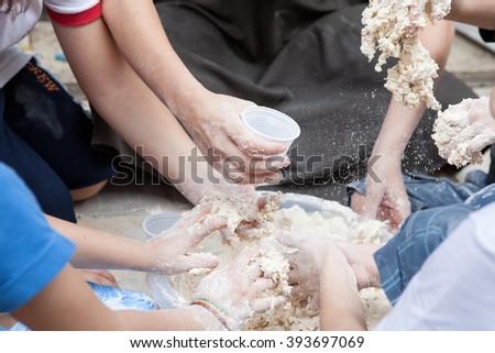 Kids with hands full of flour preparing a meal - stock photo