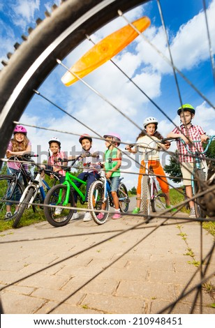 Kids with helmets hold bikes view through spoke - stock photo