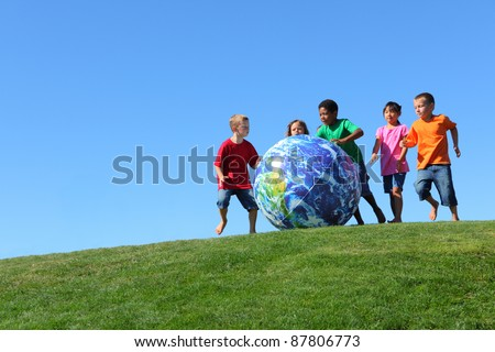 Kids with large earth ball, on grass hill with blue sky - stock photo
