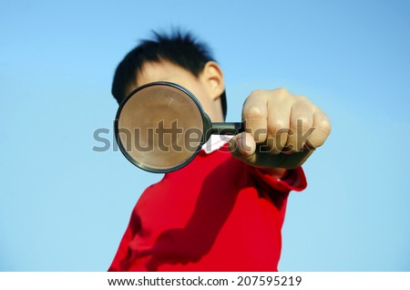 Kids with magnifying glass with sky as a backdrop. - stock photo