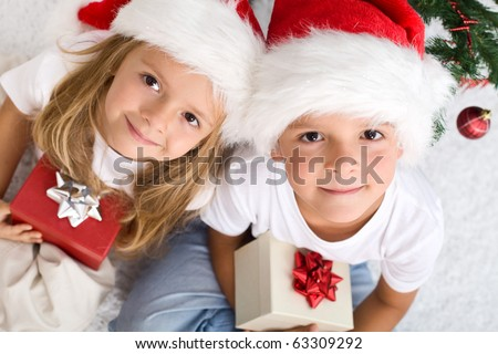 Kids with their christmas presents presents sitting on the floor - stock photo