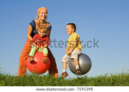 Kids with their mother jumping in the grass under clear blue sky - slight motion blur - stock photo