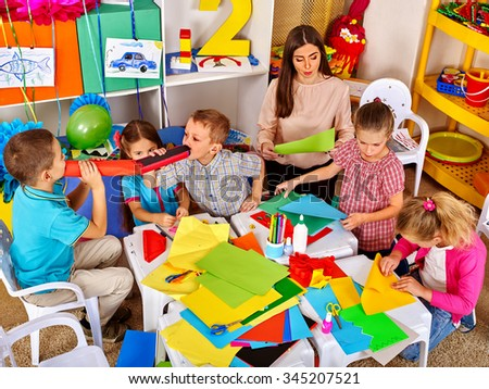 Kids with young teacher woman painting on paper at table  in  kindergarten . Top view. - stock photo