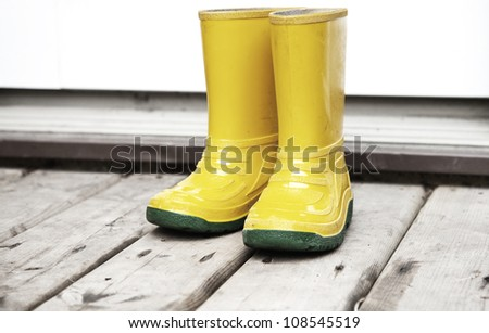 Kids yellow boots on the wooden deck entrance - stock photo