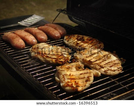 Kielbasa and chicken on the grill. - stock photo