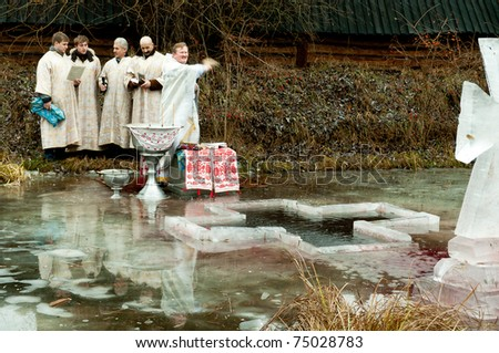 KIEV - JAN 19:  Priests in white cloth sanctify water in river at day of the Religious Christian holiday Epiphany. Holiday passes on the territory  Museum, January 19, 2011 in Kiev, Ukraine