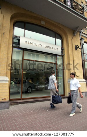KIEV - JULY 12: Two men walk past the display window of a  Bentley car dealership in Kiev, Ukraine, on Wednesday, July 12, 2006. - stock photo