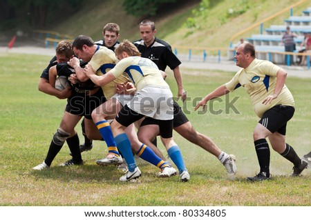 KIEV - JUNE 12: Rugby players in action at a Ukrainian National Championship rugby match, Antares(in black) vs. Argo(in yellow), June 12, 2011 in Kiev, Ukraine. - stock photo