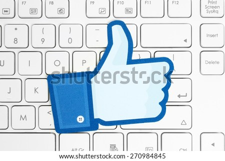 KIEV, UKRAINE - APRIL 15, 2015: Facebook thumbs up sign printed on paper and placed on white keyboard. Facebook is a well-known social networking service. - stock photo