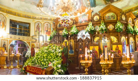 KIEV, UKRAINE - APRIL 19, 2014: The wooden iconostasis and an altar decorated with flowers of the orthodox church of Svyato-Vvedensky Monastery during the Easter, on April 19 in Kiev. - stock photo