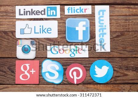 KIEV, UKRAINE - AUGUST 22, 2015:Collection of popular social media logos printed on paper:Facebook, Twitter, Google Plus, Instagram, Skype, Flickr, Pinterest, Linkedin on wooden background - stock photo