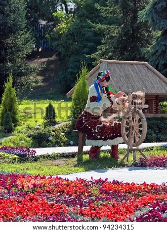 KIEV, UKRAINE - AUGUST 21: Model of a young woman made of flowers in Ukrainian national costume with spinning wheel at the 55th annual flower exhibition on August 21, 2010 in Kiev, Ukraine. - stock photo