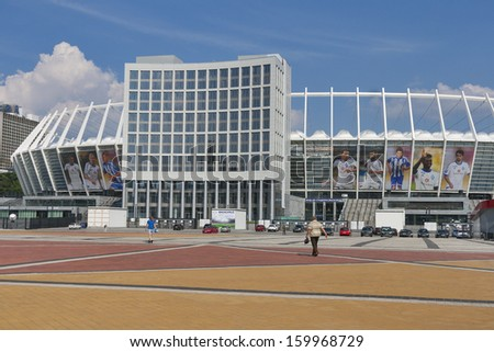 KIEV, UKRAINE - AUGUST 07: People walk along Olympic National Sports Complex hosted the final of Euro 2012 with banners of portraits of Dynamo Kiev team players on August 07, 2013 in Kiev, Ukraine. - stock photo
