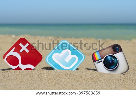 Kiev, Ukraine - August 10, 2015: Popular social media  Instagram,  Twitter and Google Plus printed on paper and placed in the sand against the sea. - stock photo