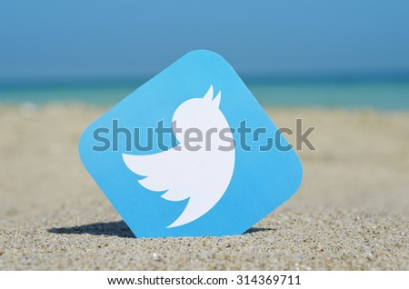 KIEV, UKRAINE - AUGUST 10, 2015:  Twitter  logotype printed on paper and placed in the sand against the sea. Twitter social network for public exchange of short messages using the web interface, SMS. - stock photo