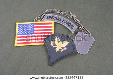 KIEV, UKRAINE - August 21, 2015.  US ARMY Specialist rank patch, special forces tab, flag patch and dog tag on olive green uniform