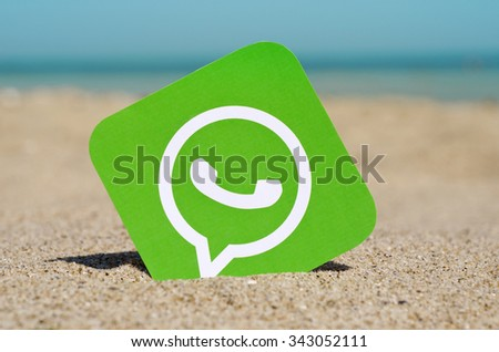 KIEV, UKRAINE - AUGUST 10, 2015: . WhatsApp proprietary messenger for smartphones printed on paper and placed in the sand against the sea.  Allows you to send text messages, images, video and audio.  - stock photo