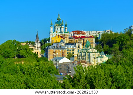 Kiev, Ukraine. Beautiful view of the ancient street Andrew's Descent and the St. Andrew's Church among green trees of the Castle Hill in Kyiv - stock photo