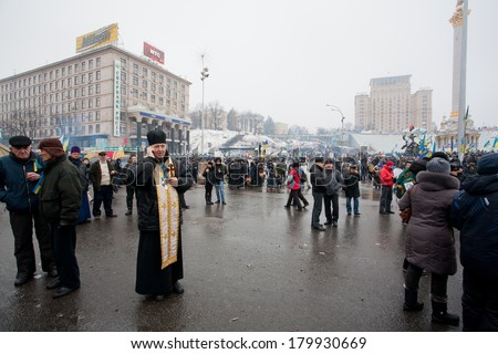 KIEV, UKRAINE - DEC 12: Catholic priests talking on a cell phone outdoor during anti-government Euromaidan protest on December 12 2013. More than 800,000 protesters participated in Kiev's Euromaidan