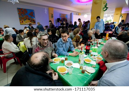 KIEV, UKRAINE - DEC 10: Different people talking at the tables at the Christmas charity dinner for the homeless on December 10, 2013, in Kyiv, Ukraine. About 100,000 adults are homeless in Ukraine. - stock photo