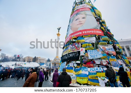 KIEV, UKRAINE - DEC 10: Huge christmas tree with banners, flags and posters on the main street occupied by demonstrators during anti-government protest Euromaidan on December 10, 2013 in Kyiv, Ukraine - stock photo