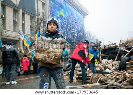 KIEV, UKRAINE - DEC 12: Unidentified boy helps to collect firewood outdoor during anti-government Euromaidan protest on December 12 2013. More than 800,000 protesters participated in Kiev's Euromaidan - stock photo