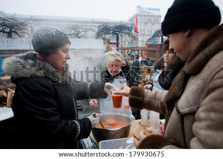 KIEV, UKRAINE - DEC 12: Women cook traditional borsch for different hungry people on the street during Euromaidan protest on December 12 2013. More 800,000 protesters participated in Kiev Euromaidan - stock photo