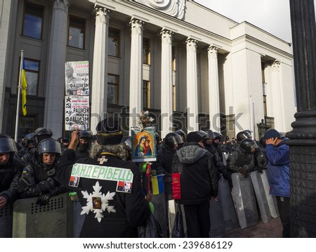"KIEV, UKRAINE - December 23, 2014: A priest with an inscription on the back ""Banderovets"" near the Verkhovna Rada. -- To break through the cordon of police and four special forces in full uniform - stock photo"