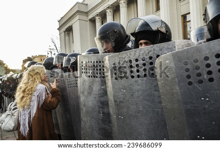 KIEV, UKRAINE - December 23, 2014: Woman talking with the National Guard. -- To break through the cordon of police and four special forces in full uniform - stock photo