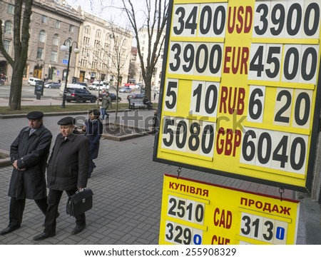 KIEV, UKRAINE - Feb 25, 2015: People passes the currencies exchange rate plate downtown Kiev. Ukraine's hryvnia plummeted more than 100 percent against the dollar to new record low on January 6, 2015 - stock photo