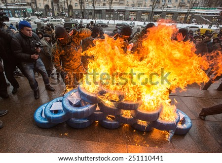 KIEV, UKRAINE - FEBRUARY, 9, 2015: A group of unidentified men in camouflage burn tyres outside City Hall in protest of the increase of fares on public transport  - stock photo