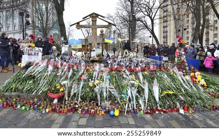 KIEV UKRAINE -FEBRUARY 22, 2015: Anniversary of mass shooting the armless  Euromaidan demonstrators by armed special forces. Memorial Gallery under Cross, flowers and sorrowing peoples