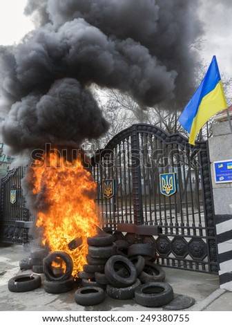 KIEV, UKRAINE - February 2, 2015: Fighters of volunteer's battalion 'Aydar' throw tyres on a burning stack during a protest rally in front of Ukrainian Ministry of Defense in Kiev.  - stock photo