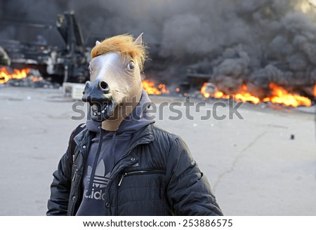 KIEV UKRAINE-FEBRUARY 18, 2014: Fire protecting by defend oneself protesters of  armed special forces attack at first day of mass shooting at Euromaydan time. Unknown protester in mask of horse head