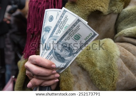 KIEV, UKRAINE - FEBRUARY, 12, 2015: Participant of the meeting against the devaluation of the Ukrainian national currency keeps a pack of souvenir dollars - stock photo