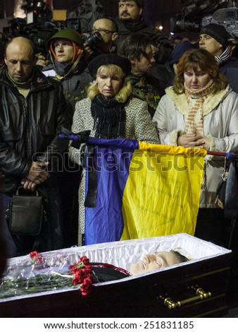 Kiev, Ukraine - 22 February 2014: People attend the funeral ceremony at Independence Square for anti-government protesters who were killed during protests in downtown Kiev - stock photo