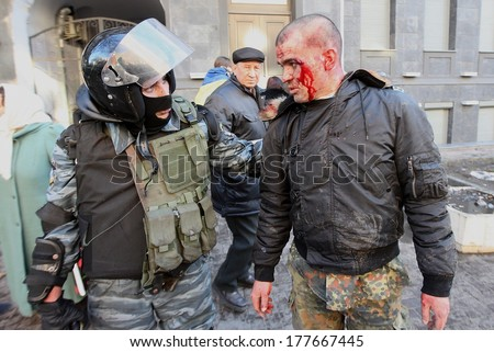 KIEV, UKRAINE - FEBRUARY 18, 2014: Policeman talks to protesters injured person. Kiev, Ukraine, Kiev, 18.02.2014