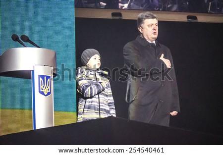 KIEV, UKRAINE - February 20, 2015: President of Ukraine Petro Poroshenko with Vladislav Tsipun, son of the hero of Heaven hundreds the Hero of Ukraine Andriy Tsipun performs the National Anthem - stock photo