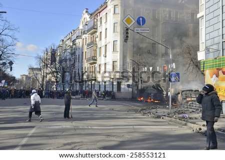 KIEV UKRAINE FEBRUARY 18, 2014: The first day of mass shooting of Euromaydan protesters.The unarmed marchers on Institutska street protect themselves after first attack of armed special forces