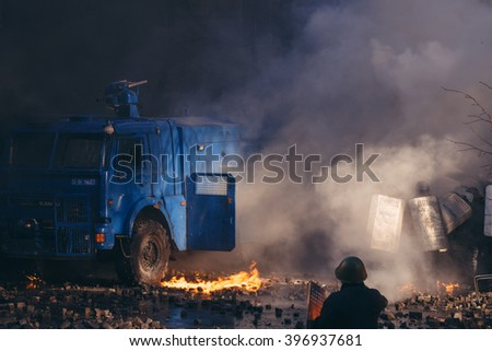 Kiev, Ukraine - 18 February 2014: ukrainian protesters trying to burn water cannon and throwing cobblestones at riot police to stop them. During violent confrontation on Instytutska Street.