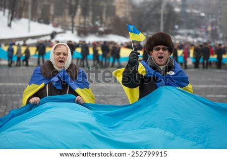 KIEV, UKRAINE - FEBRUARY, 15, 2015: Woman and man holds flag during the march. Thousands people went with the 200-meter flags of Ukraine and Lithuania on Khreschatyk and Independence Square. - stock photo
