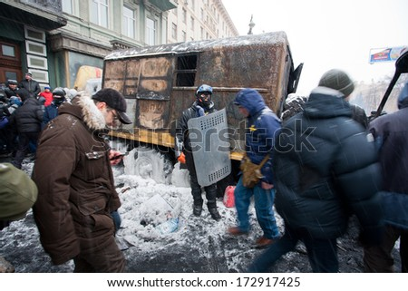 KIEV, UKRAINE - JAN 21: Active protester with shield and mask stands near the burned military auto on the winter street during anti-government riot Euromaidan on January 21, 2014, in Kyiv, Ukraine.  - stock photo