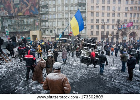 KIEV, UKRAINE - JAN 21: Crowd of active people guard the winter street in city center with burned transport during winter anti-government protest Euromaidan on January 21, 2014, in Kyiv, Ukraine  - stock photo