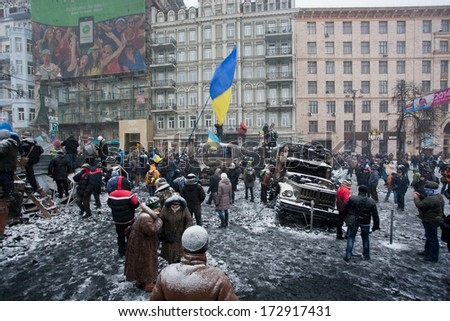 KIEV, UKRAINE - JAN 21: Crowd of people protest with flags on the burned snowy street during long winter anti-government protest Euromaidan on January 21, 2014, in downtown of Kyiv, Ukraine  - stock photo