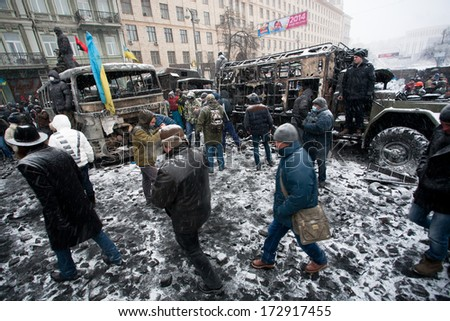 KIEV, UKRAINE - JAN 21: People walking inside the burned part of city with broked cars and buses in snow during winter anti-government protest Euromaidan on January 21, 2014, in Kyiv, Ukraine  - stock photo