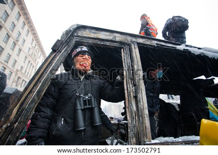 KIEV, UKRAINE - JAN 21: Young protester with binoculars in mask watch from a broken window of burned military car during anti-government protest Euromaidan on January 21, 2014, in Kyiv, Ukraine - stock photo