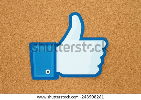 KIEV, UKRAINE - JANUARY 10, 2015: Facebook thumbs up sign printed on paper and placed on cork bulletin board. Facebook is a well-known social networking service. - stock photo